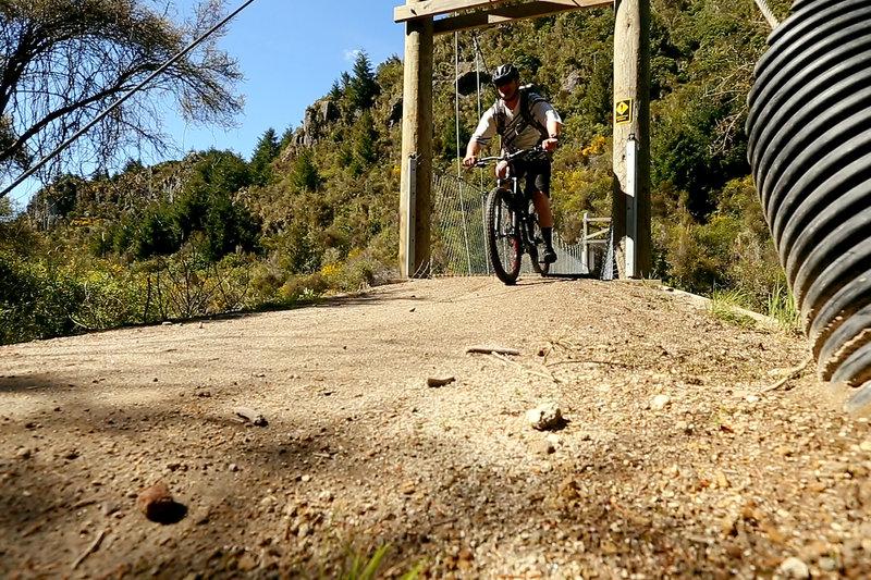 Crossing the swing bridge at the start of the Waihaha Mountain Bike Trail