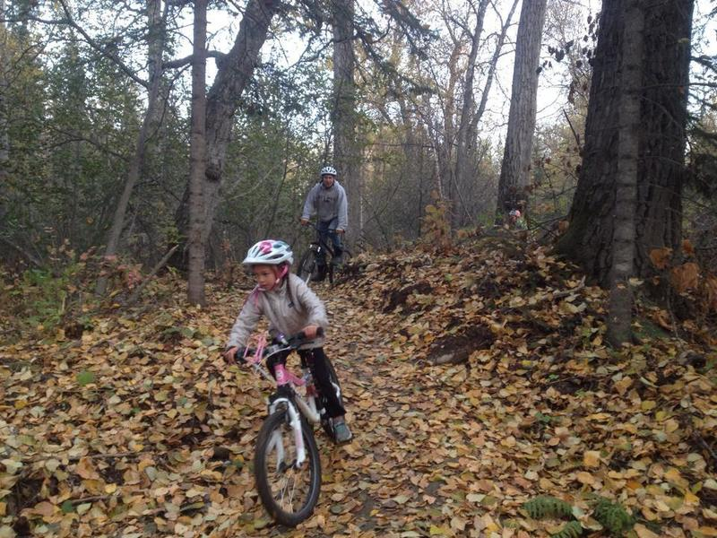 """Family riders riding the """"Tech Trail"""" in fall leaves"""