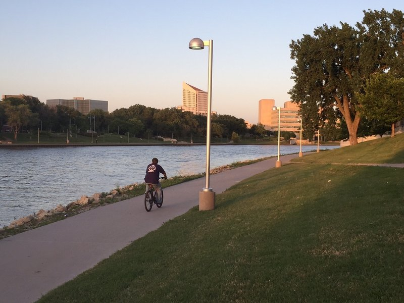West side of the downtown river path, across from the Keeper of the Plains