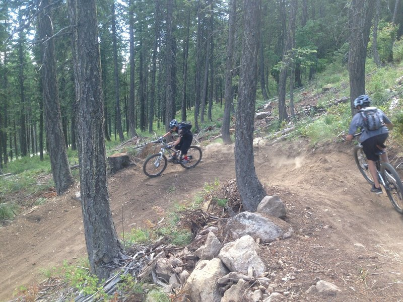 Couple of youngsters flying through the bermed corners inf the new upper section of the trail
