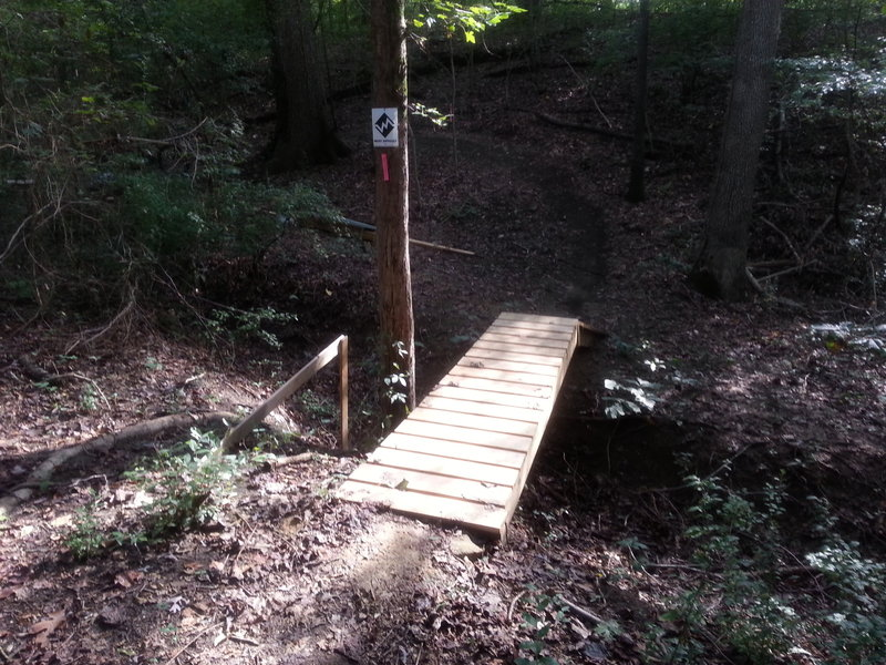 Wooden kicker bridge over a small ravine.