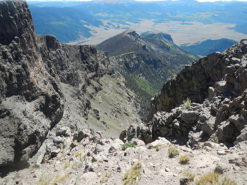 The plunging escarpment off Bristol Head (12706'). The road to Creede, Colo., is in the distance.
