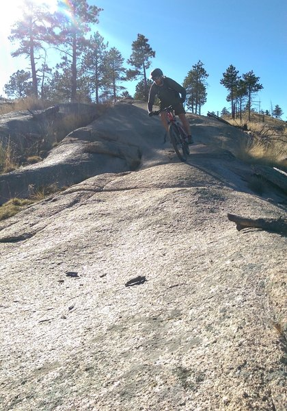 Short descent on a rock outcropping on the Homestead Trail. Watch out for loose sand at the bottom.