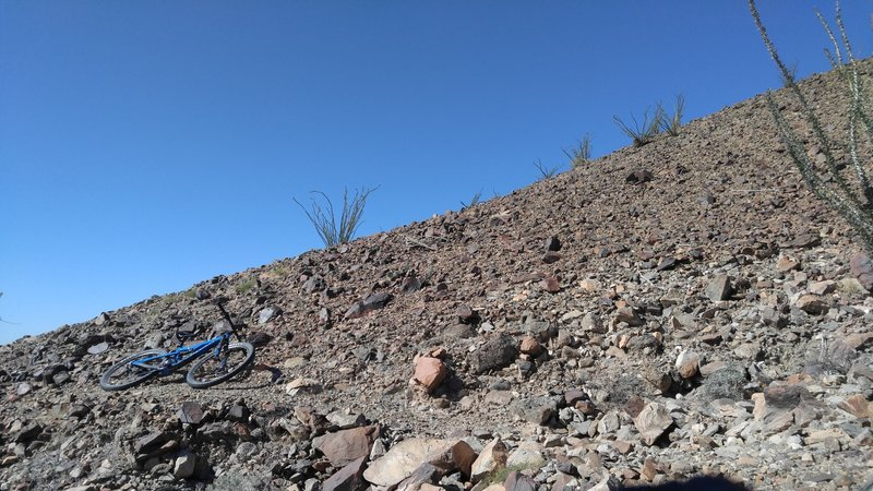 I recently found this bit of old trail where a segment of Ryan has been obscured by mining operations. It is across the wash, north of where Ryan is mapped now. Experienced riders will find most of it rideable.  Both ends need reclamation to connect with the currently mapped route.