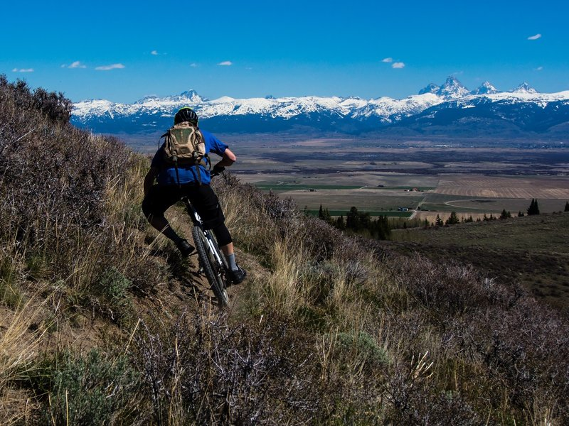 Rider Jake Hawkes get his XC on in the Big Hole Mountains' Lower Horseshoe Canyon network with views of Teton Valley and a snowy Teton Range. Photo: Dana Ramos - Instagram: @dnasince1979