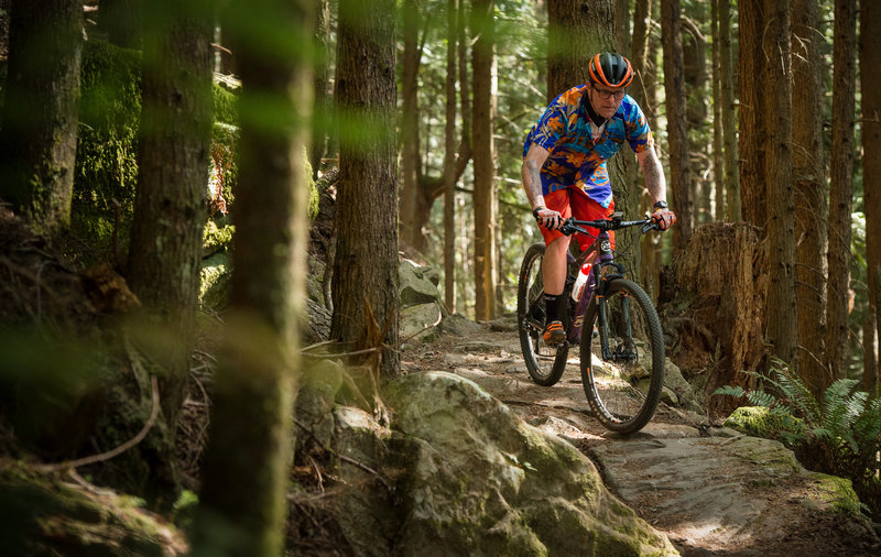 A brightly colored rider navigates a short rock ramp on the Raptor Ridge Trail.