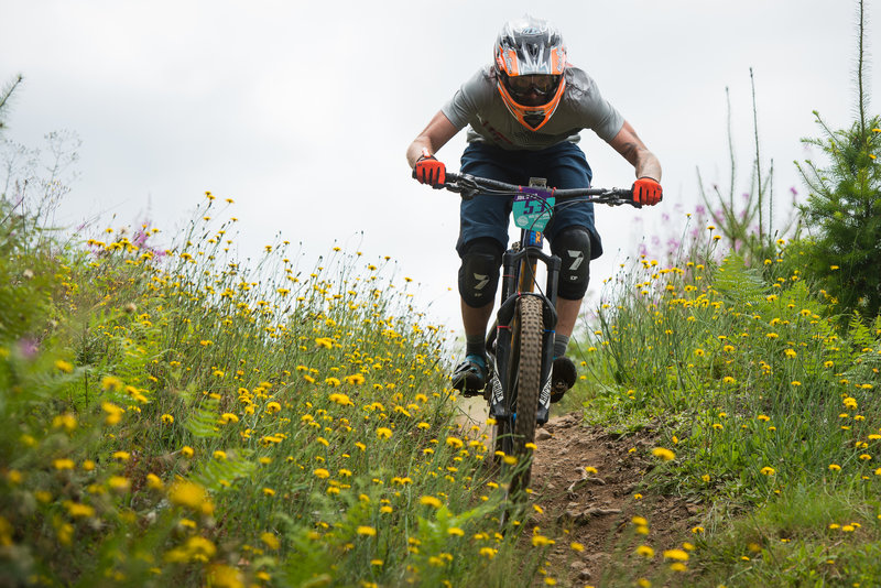 Eric Dukes flies past spring blooms on Thrillium during the Cascadia Dirt Cup.