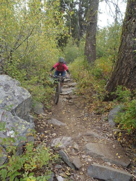 Liz rides a rocky chute.