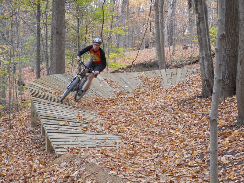 Berm feature on Hampton Hills Intermediate Trail heading downhill towards Woodward Creek.