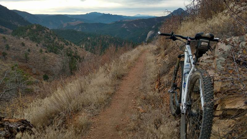 Pikes Peak in the background; the trail snakes down the valley.