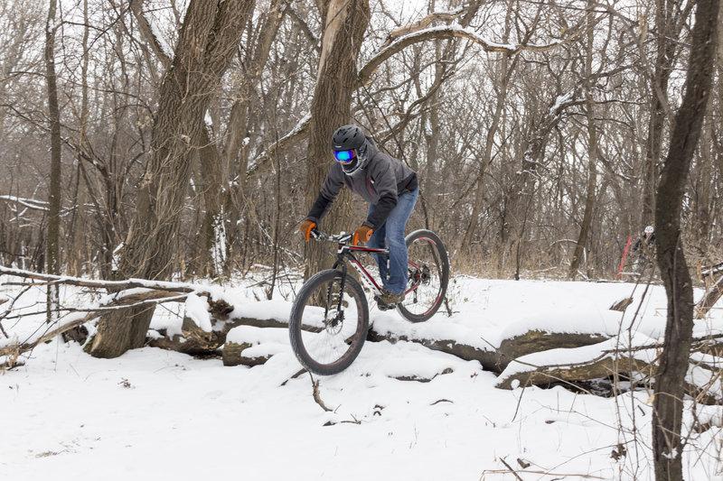 Cody rides down a log roll in a snowy M.B. Johnson Park.