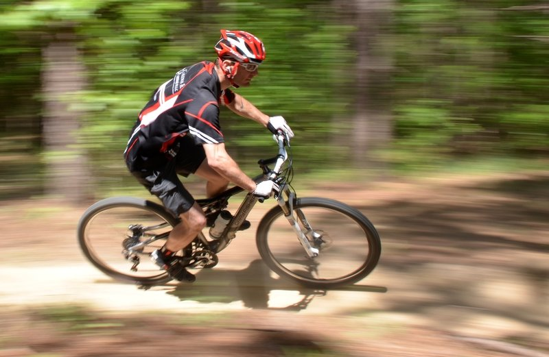 """""""Dust N Bones"""" is Mount Zion's annual race which is part of the MORCS series. This racer is enjoying the flowing downhill section near the beginning of the trail."""
