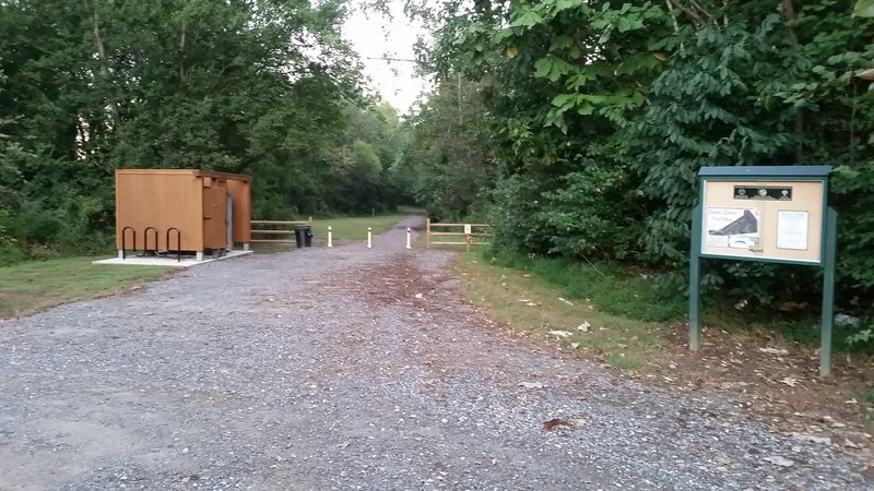 This is the trailhead from the parking lot. A Port-a-John and changing area are located to the left.