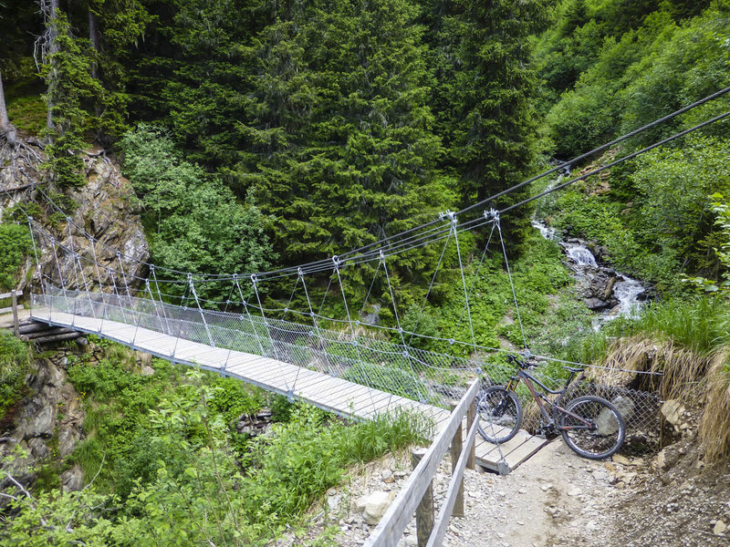 Get ready for a suspension bridge over Witibach Creek in the middle of the fun, forested singletrack section between Sertig and Clavadel.