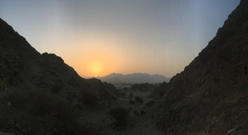 The sun rises over craggy hills in Oman.