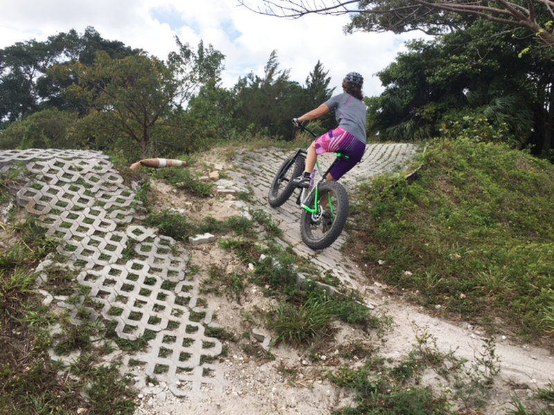 Julia pedals up a section of paver-stone berms and turf-block rollers. The SoFla builders find ingenious ways to vary the flat terrain.
