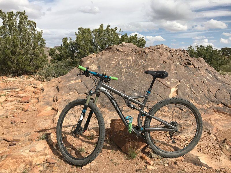A wall of nearby petroglyphs carved into the rock. Be sure to carefully walk your bike through this area and do not disturb these precious windows into the past.