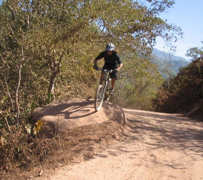 Chaz rides over a large road-side boulder.
