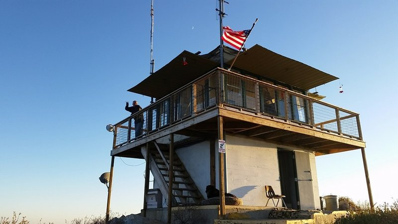 The custodian of the lookout tower waves good bye on a sunny evening.