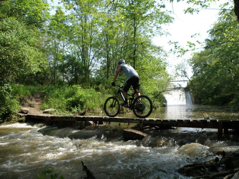 Riding the narrow spillway bridge across Spring Creek.