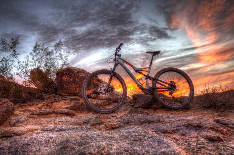 A brilliant sunset behind petroglyph rocks.