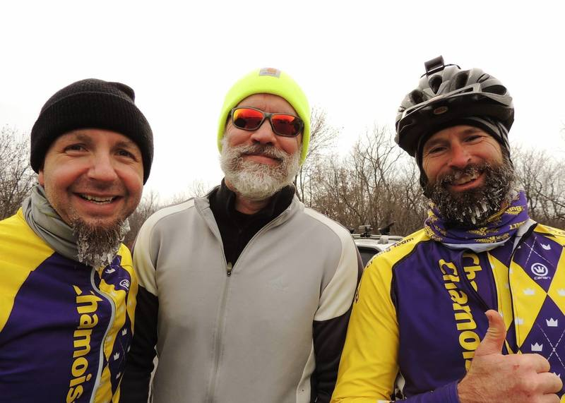 Three guys just riding bikes in the winter.