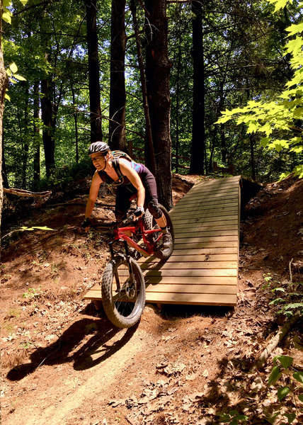J. riding through wooden drop option on the Basic Training Skills Trail.