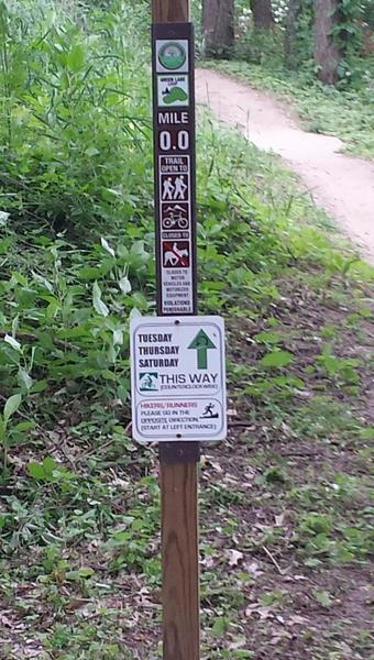 Directional sign at trailhead; trail direction alternates daily
