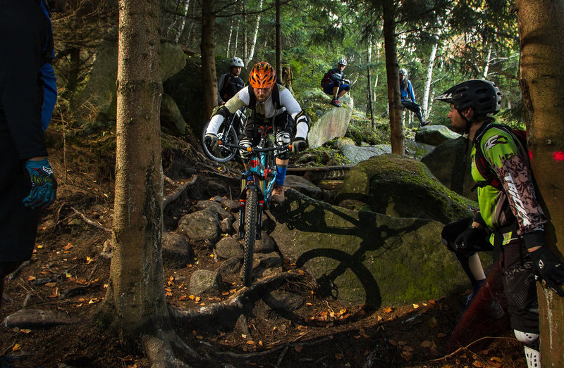 A rider takes a skills lesson on the rough Wales trail.