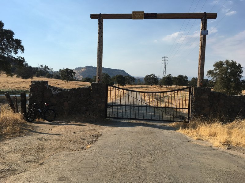 This is the gate at the top of the trail. It is locked. On the left, there is a narrow gap you can walk through and you have to lift your bike over your head to get through. Then start riding down the dirt road.