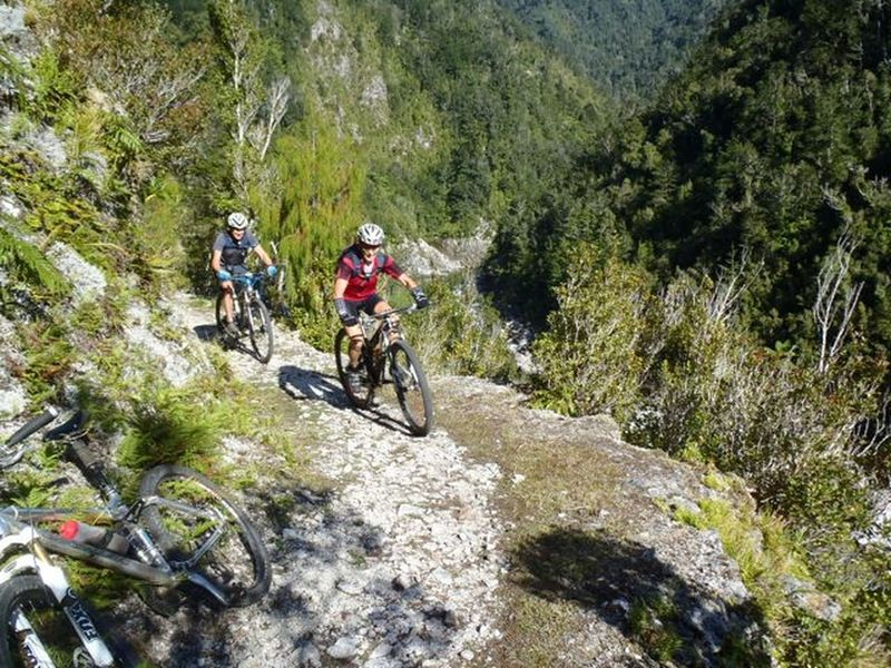 The track clings precariously to a cliff face high above the Mokihinui River.