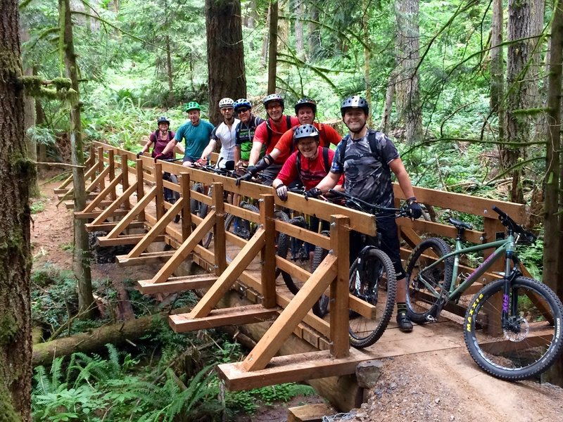 """NW Trail Alliance ride group posing on the newly completed """"Link'n'Pin"""" bridge on Shoofly over Genzer Creek"""