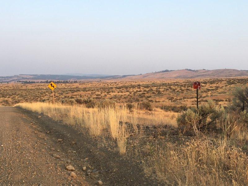 "Parking for Manastash Backside trails.  Look for the trail behind the shot up ""Fiber optic"" sign shown here."