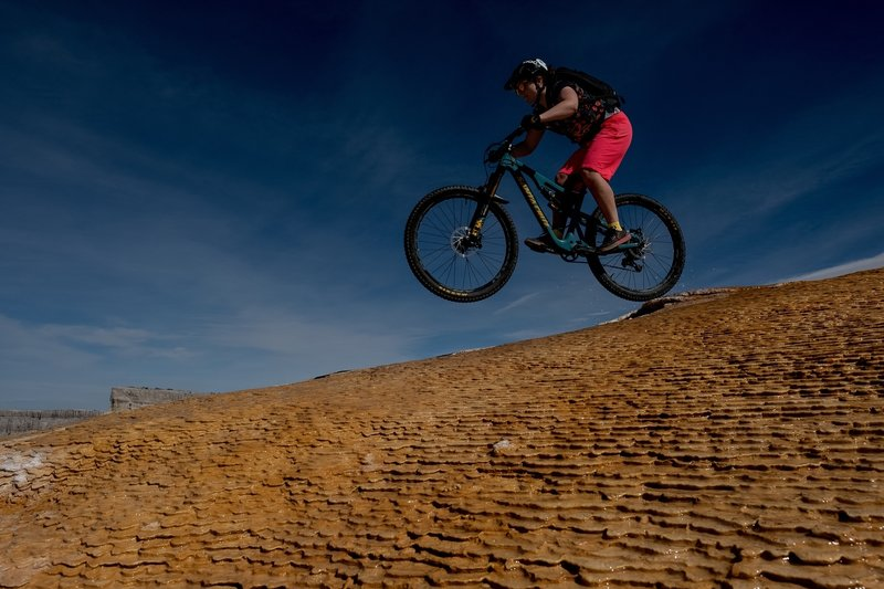 Lizz getting some air under her wheels while descending Good Times at White Mesa.