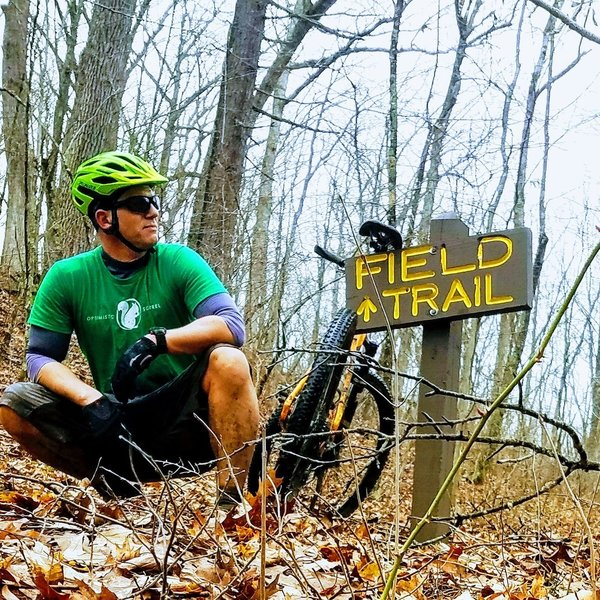 The trail sign near where Field Trail intersects with a paved road in Shawnee State Park.