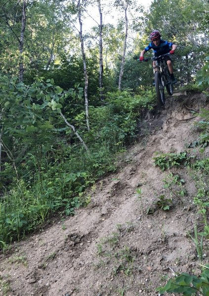 Riding a drop in the skills area at the end of the trail