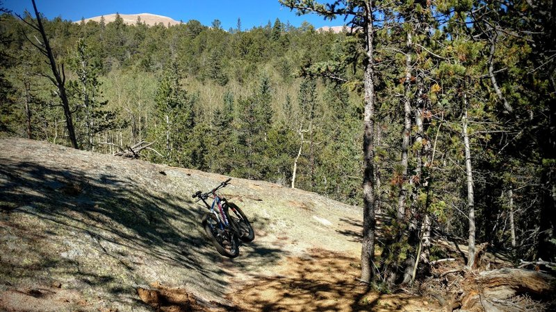 Pike's Peak tops above one of the massive granite boulders along the Lake Moraine trail. The trail has numerous A and B lines, truly a trail built by mountain-bikers for mountain-biking!