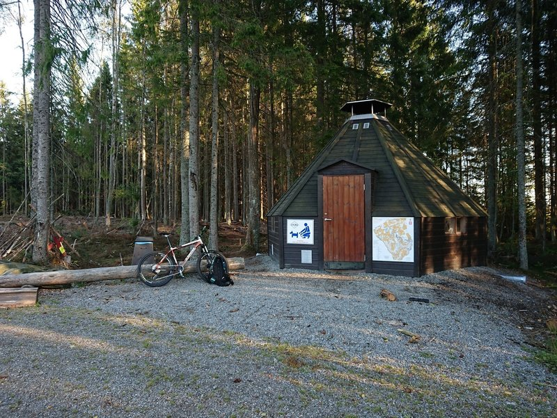 a look at hte whole rest stop area, grill hut & log bench, garbage can on behind the logbench.