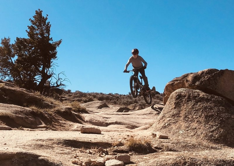 """Enjoying the section """"Behind the Rocks"""" playing on one of the many fun rocks on the side of the trail, unlimited number of optional lines you can make at this trail System on the slick rock!"""