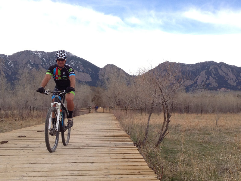 Crossing the bridge on South Boulder Trail with the Flatirons in the background.