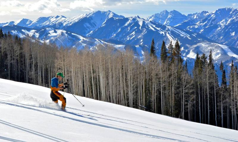 Skiing the gentle slope of the Van Horn Park meadows with the Elk Range in the background.