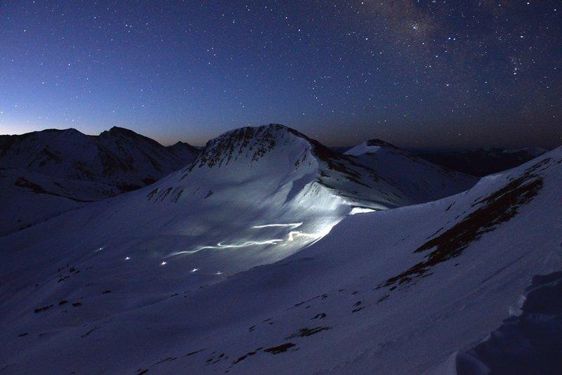 Skiers descending the backside Star Pass.