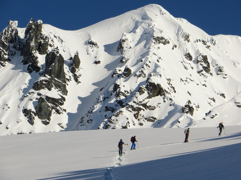 Skiers head up the flat portion of the ridge below Peak 8100. The route continues up the prominent ridge behind them.