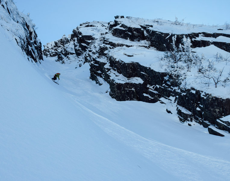 A skier carves through the bottom of the Couloir des Légend.