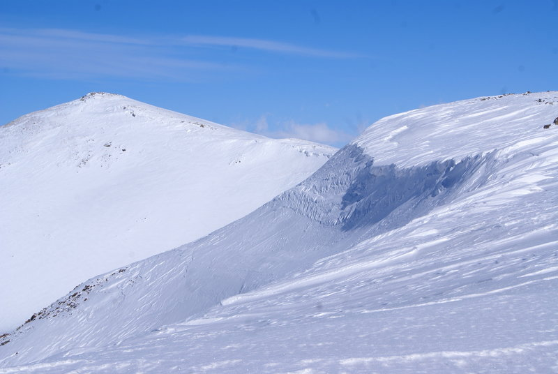 A cornice seen from afar on a blue sky day.