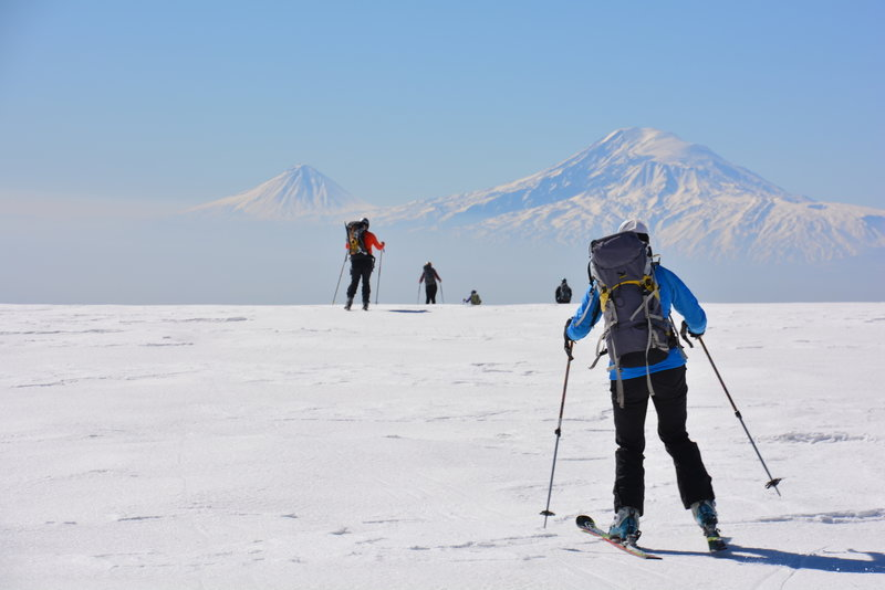 Spectacular views in the distance as skiers make their way across a flat section.