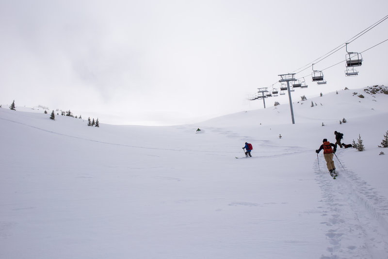 The first to climb Kachina Peak enjoy fresh April powder on Main Street, as the second group looks on from the skin track