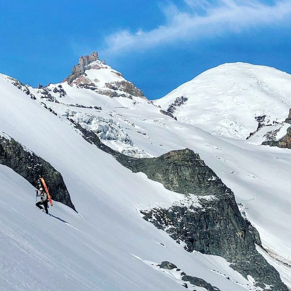 Vik Sahney ascending an icy steep section enroute to Little Tahoma; Mt. Rainier looms in the background (Photo Credit - Gavin Woody)