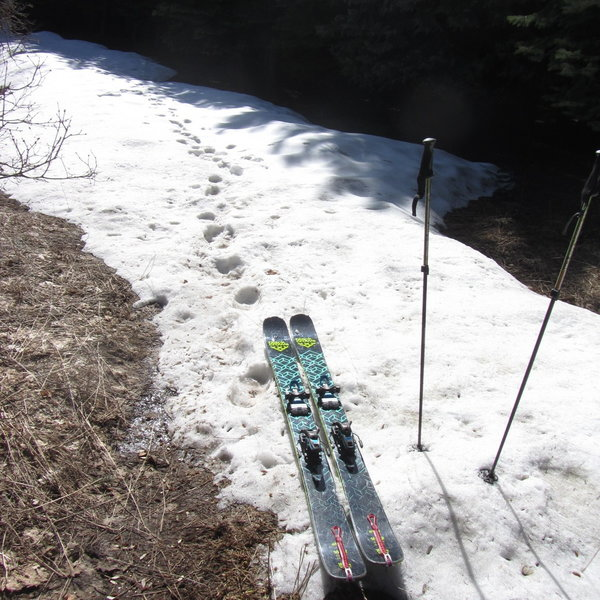 In spring, you boot the dirt until you find snow, then start skinning.  You may have to transition between walking and skinning a few times before the snow becomes consistent.