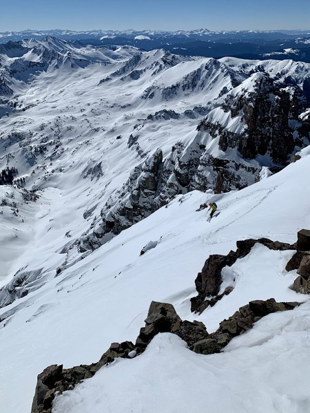 Skiing the exposed snowfield above the chutes on the east face of Castle Peak.